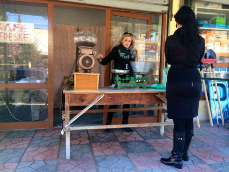 An Albanian woman selling fresh ground coffee outside her shop.
